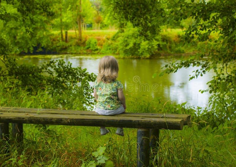 Een meisje van twee jaar oude zittings alleen op de bank en het kijken op het meer stock foto's