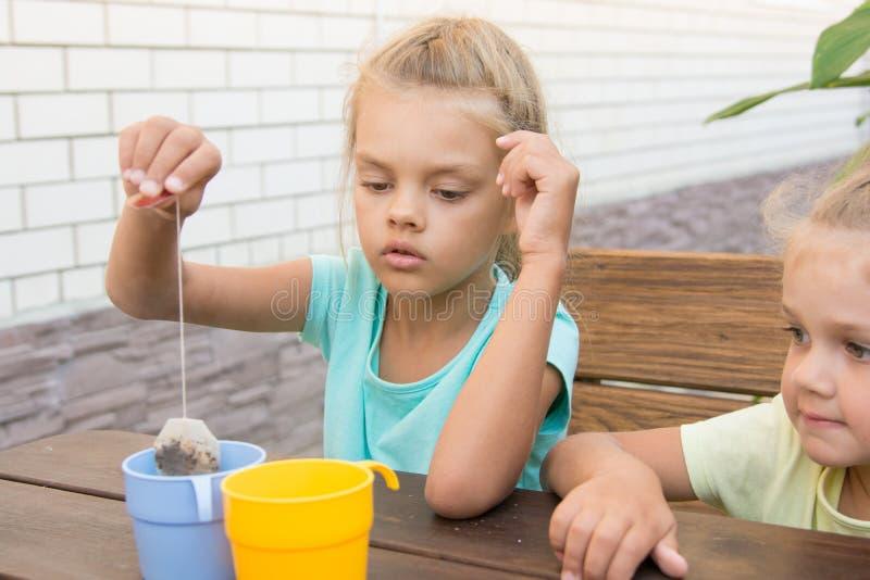 Een meisje van zes jaar van het brouwen van een kop thee van zak royalty-vrije stock foto's