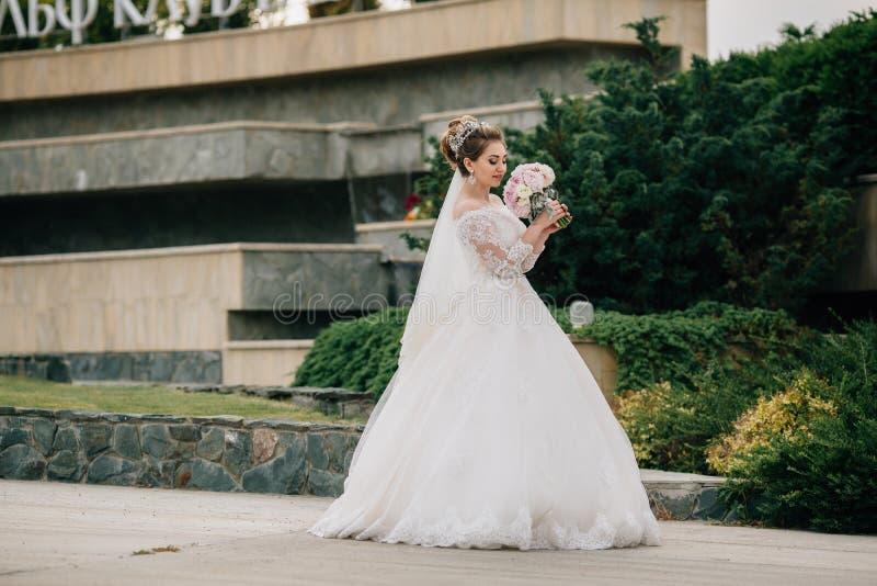 Een meisje in een weelderige huwelijkskleding met borduurwerk en kant spint in het park, inhalerend het aroma van haar boeket van stock foto
