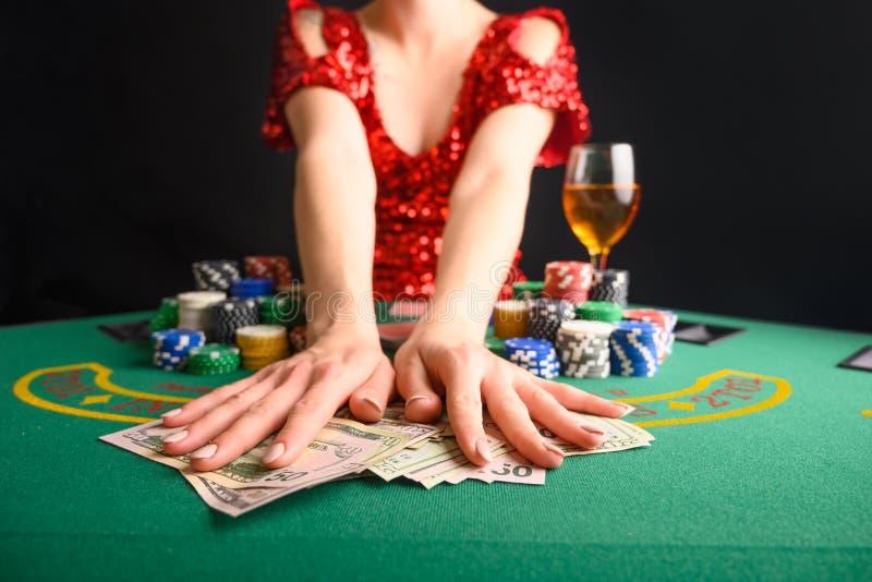 Een meisje wint kaarten in een casino en neemt wins, geld, dollars weg Blackjack poker sms-poker gamebusiness stock foto