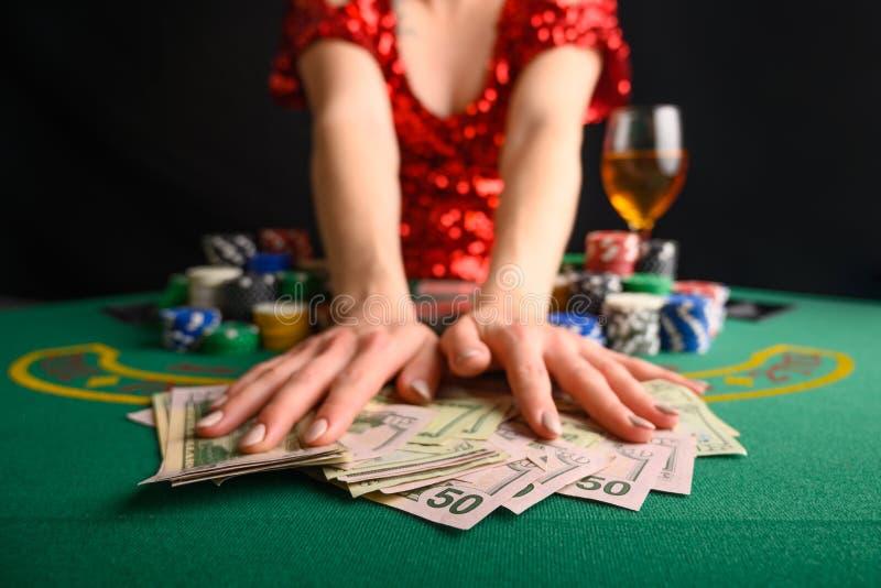 Een meisje wint kaarten in een casino en neemt wins, geld, dollars weg Blackjack poker sms-poker gamebusiness stock foto's