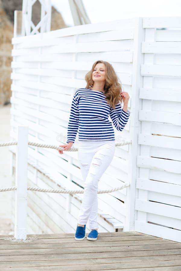 Een meisje in witte strakke jeans en sportenschoenen die tegen een witte houten muur stellen In een zeemanst-shirt en glazen krul royalty-vrije stock afbeeldingen