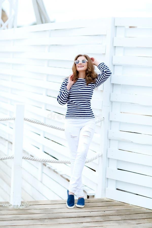 Een meisje in witte strakke jeans en sportenschoenen die tegen een witte houten muur stellen In een zeemanst-shirt en glazen krul stock fotografie