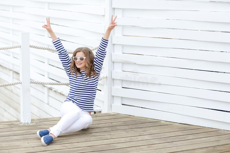 Een meisje in witte strakke jeans en sportenschoenen die tegen een witte houten muur stellen In een zeemanst-shirt en glazen krul royalty-vrije stock foto's