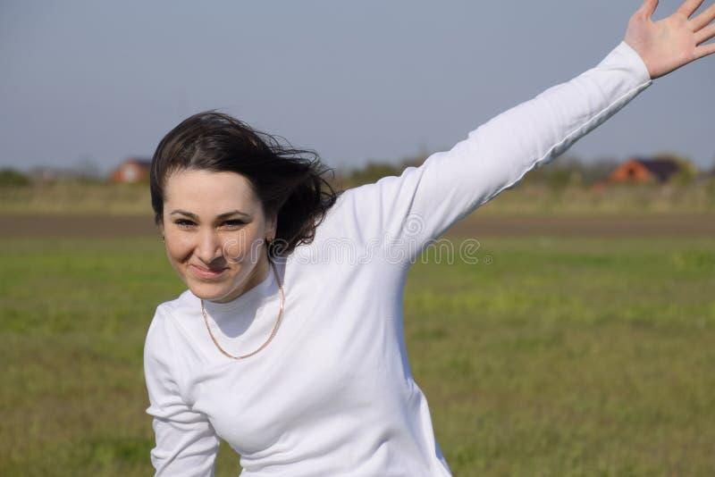 Een meisje in een witte sweater die haar hand golven en vrolijk royalty-vrije stock afbeelding