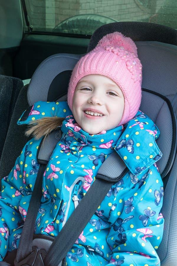 Een meisje zit als miniatuurautovoorzitter, het glimlachen stock foto's