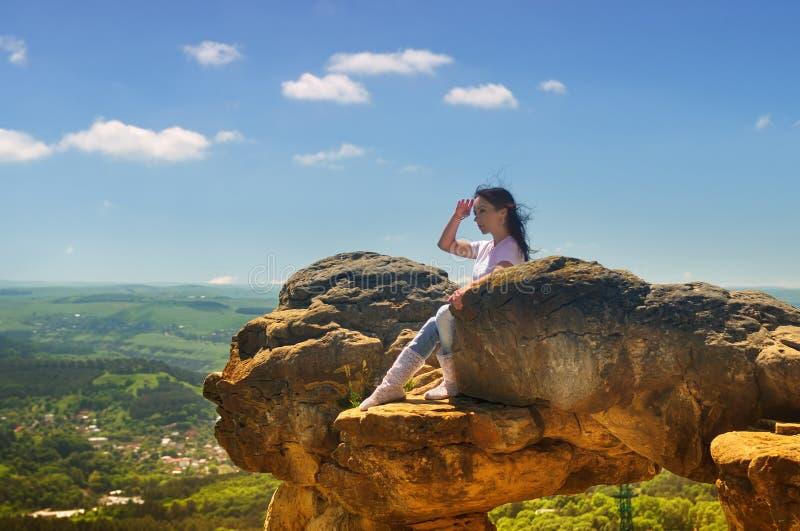 Een meisje zit op de rand van een klip en het onderzoeken van de afstand royalty-vrije stock foto's