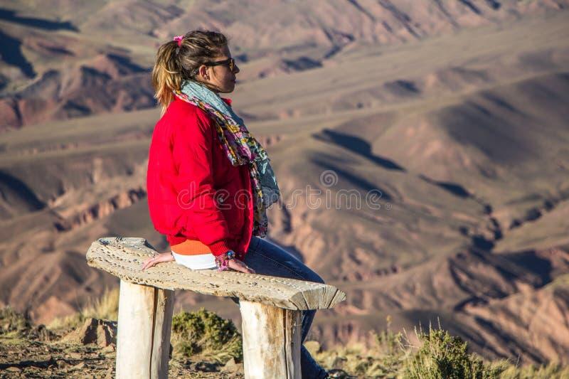 Een meisje zit op een bank in de bergen stock foto