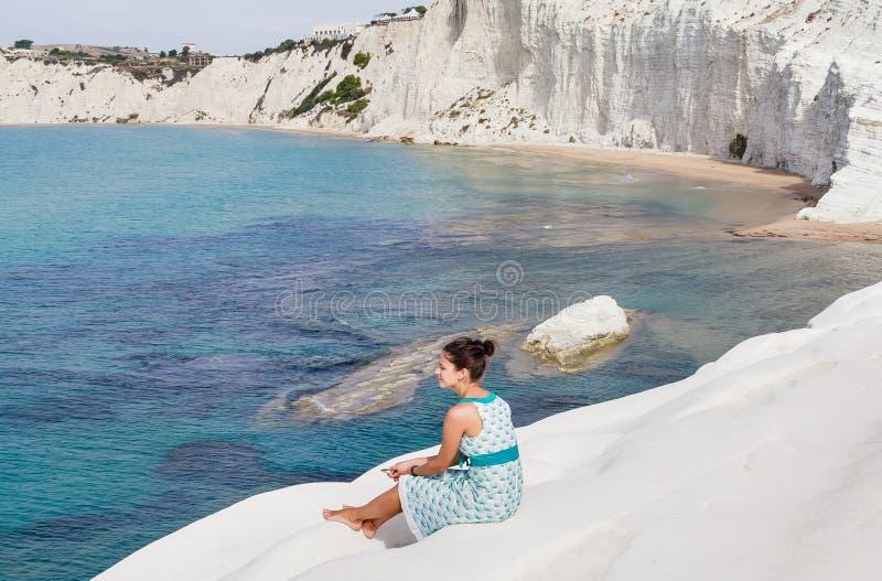 Een meisje zit op een geroepen helling van witte klip & x22; Scaladei Turchi& x22; in Sicilië stock afbeeldingen