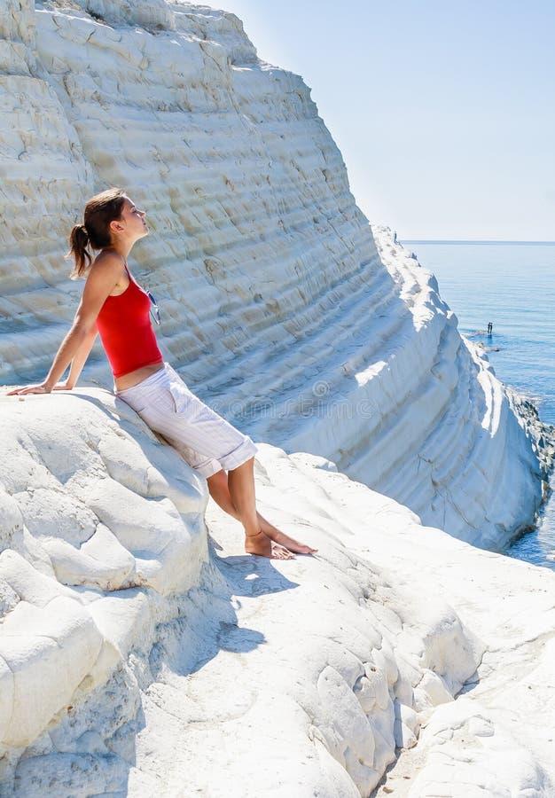 Een meisje zit op een geroepen helling van witte klip & x22; Scaladei Turchi& x22; in Sicilië, royalty-vrije stock afbeelding
