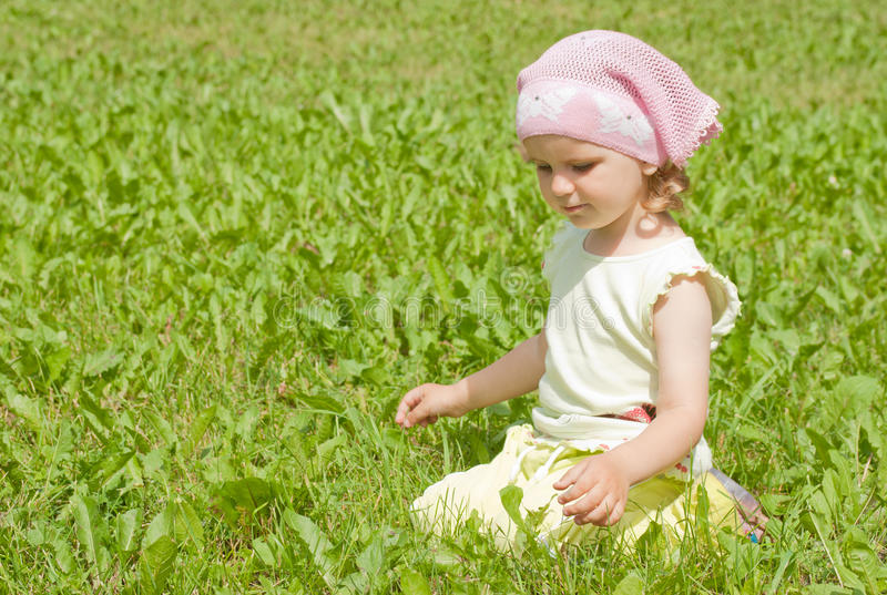 Een meisje zit op een groen gazon royalty-vrije stock afbeelding