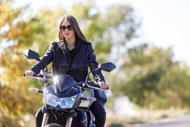 Een meisje zit op een motorfiets in zwarte leerkleren stock foto