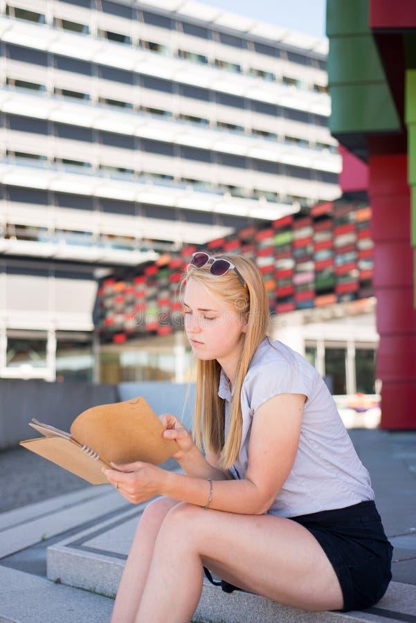 Een meisje zit op stappen met notitieboekje royalty-vrije stock foto