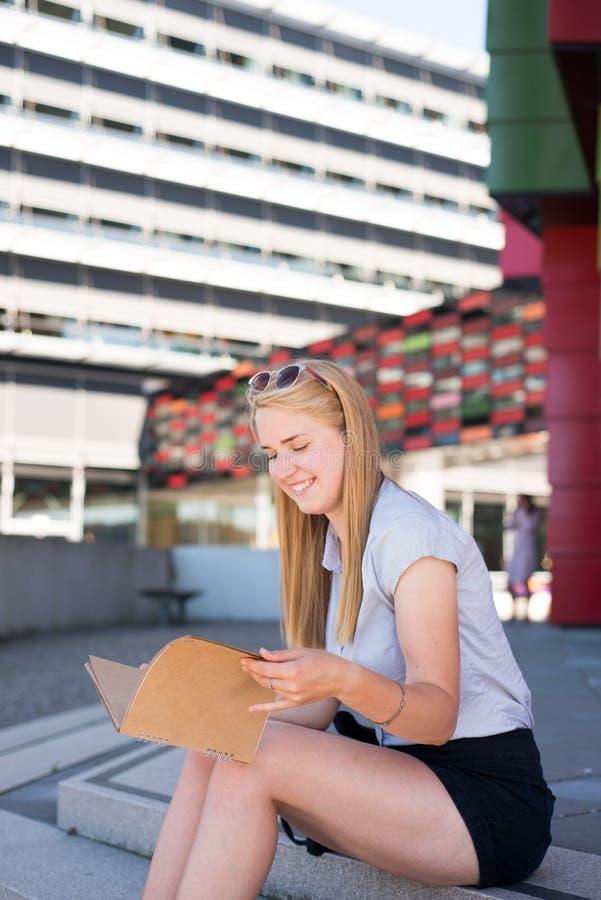 Een meisje zit op treden terwijl het kijken op notitieboekje stock afbeeldingen