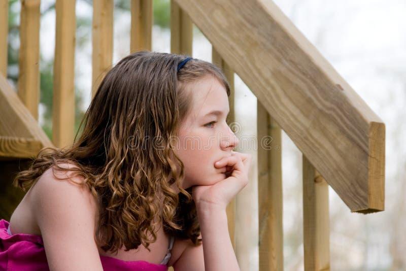 Een meisje zitting en het denken stock foto
