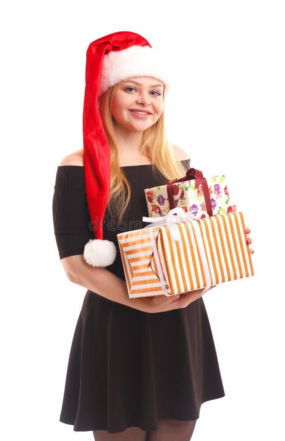 Een meisje in een zwarte kleding en in een Kerstmanhoed houdt giftdozen Geïsoleerde royalty-vrije stock afbeeldingen