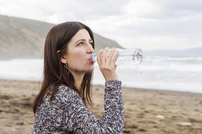 Een meisjes drinkwater in het strand stock foto
