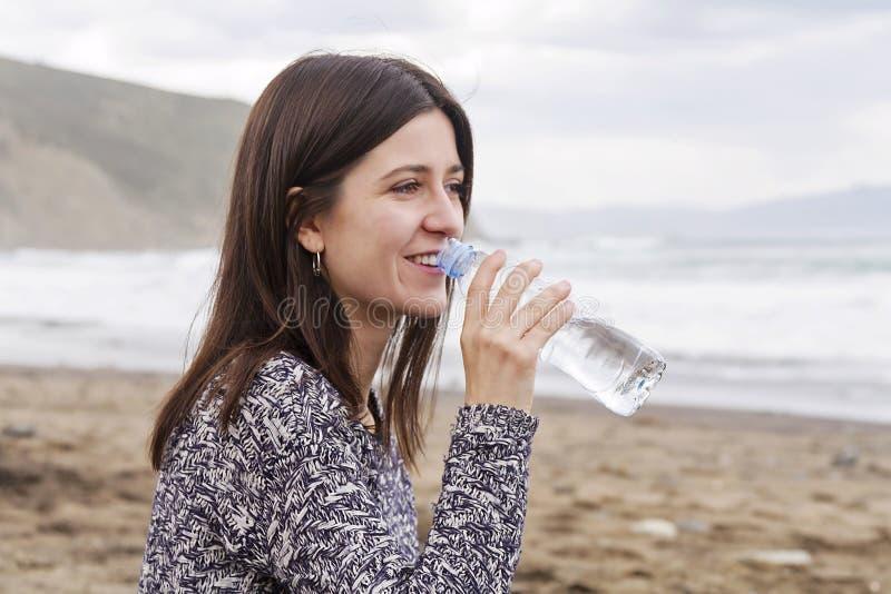 Een meisjes drinkwater in het strand royalty-vrije stock foto's