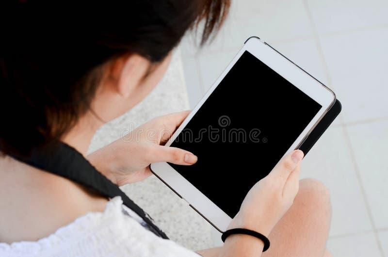 Een meisjeshand houdt witte digitale tablet in het park stock foto