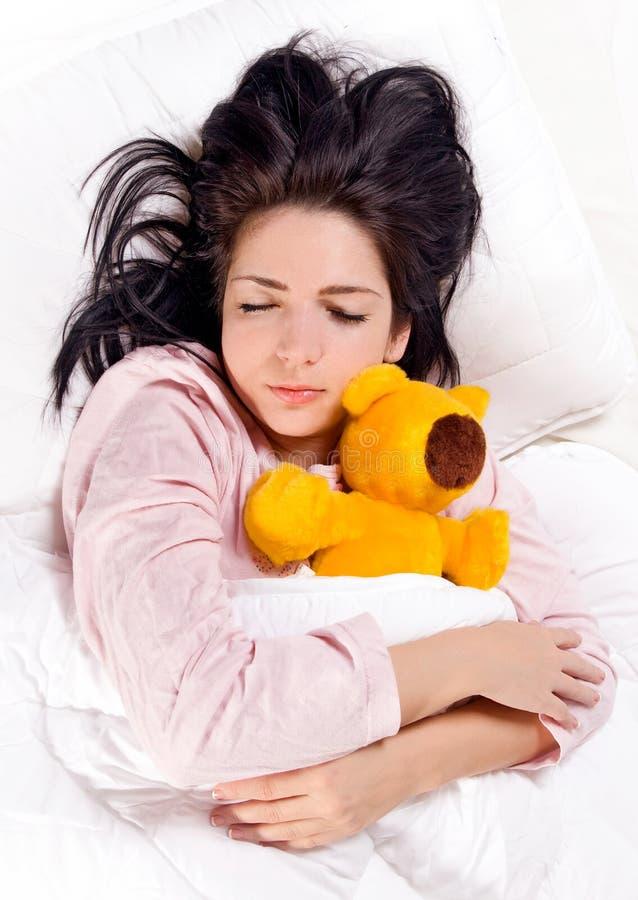 Een meisjesslaap met teddybeer in het bed stock foto