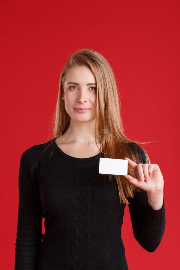 Een meisjesvertegenwoordiger, houdt een leeg adreskaartje met een lichte glimlach royalty-vrije stock foto's