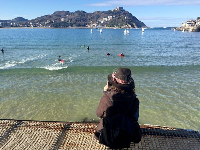 Een meisjeszitting op de pijler van donostia-San Sebastian, Baskisch Land, Stad, Spanje Het strand van het panorama van La Concha royalty-vrije stock foto