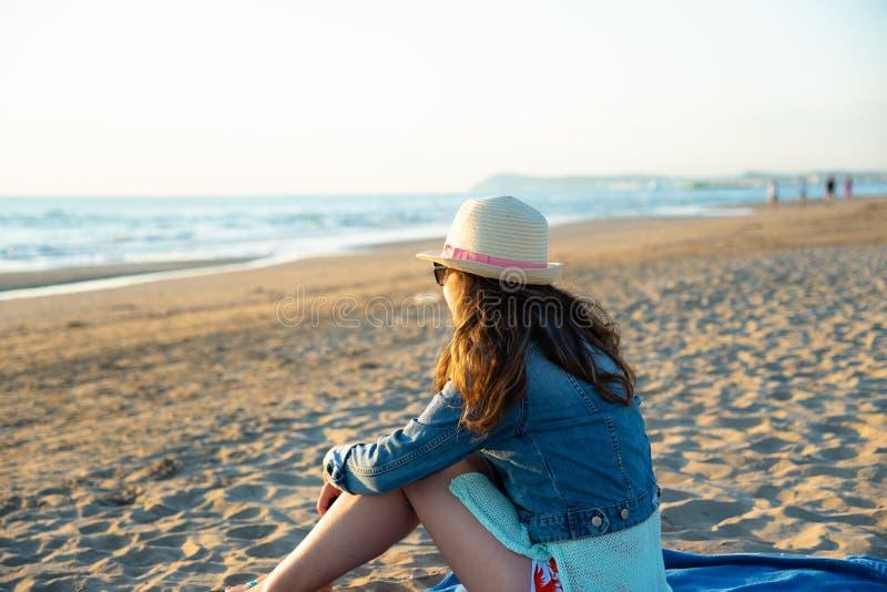 Een meisjeszitting op het strand bij de zonsopgang, bewonderend en enjoyin royalty-vrije stock fotografie
