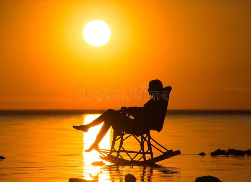 Een meisjeszitting in een rieten schommelstoel tegen de zonsondergang stock foto's
