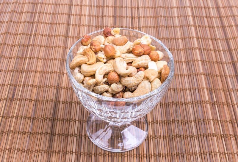 Een mengsel van cashewnoten, amandelen, hazelnoten in een wijnglas stock foto's