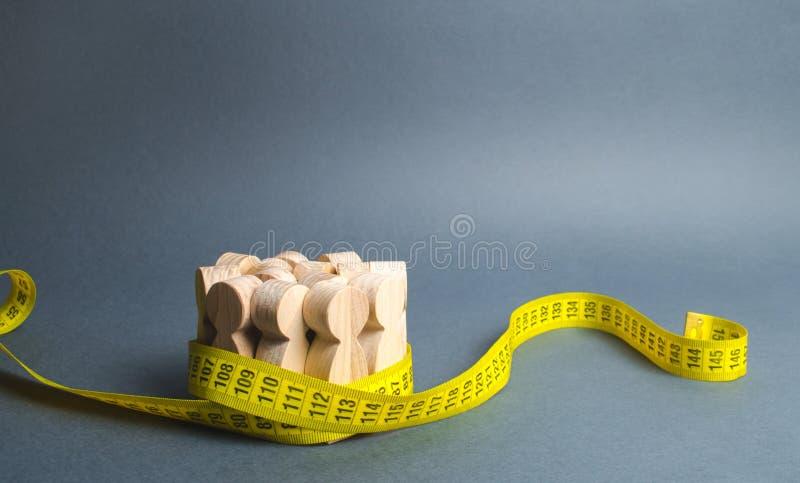 Een menigte van houten cijfers die door band worden gegrepen te meten Sociale wetenschappen Bevordering van ideeën voor gewichtsv royalty-vrije stock foto's