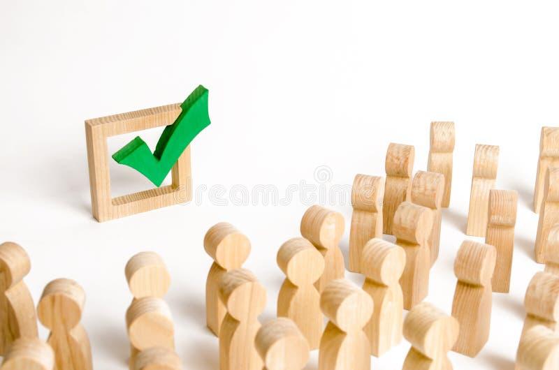 Een menigte van mensen bekijkt een groen vinkje Stemming en verkiezing concept Referendum, revolutie Gedwongen omverwerping van m stock foto