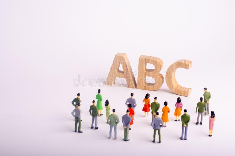 Een menigte van mensen bevindt zich en bekijkt de brieven van het alfabet ABC Beschikbaar onderwijs, kleuterscholen en scholen, royalty-vrije stock foto