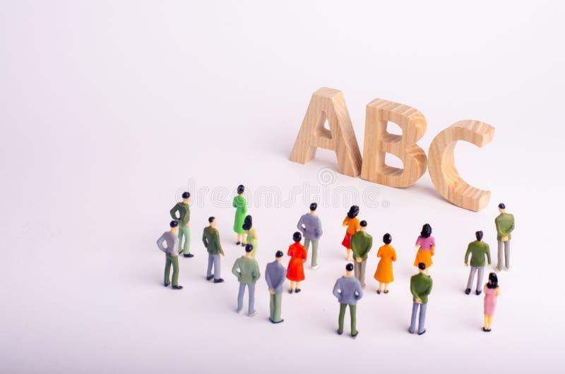 Een menigte van mensen bevindt zich en bekijkt de brieven van het alfabet ABC Beschikbaar onderwijs, kleuterscholen en scholen, c royalty-vrije stock afbeelding
