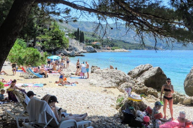 Een menigte van mensen die van een mooie de zomerdag genieten die en op een zandig strand buiten Dubrovnik, Kroatië zonnebaden zw stock afbeeldingen