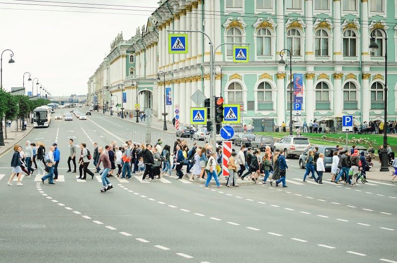 Een menigte van mensen kruist de weg bij een voetgangersoversteekplaats in St. Petersburg royalty-vrije stock fotografie