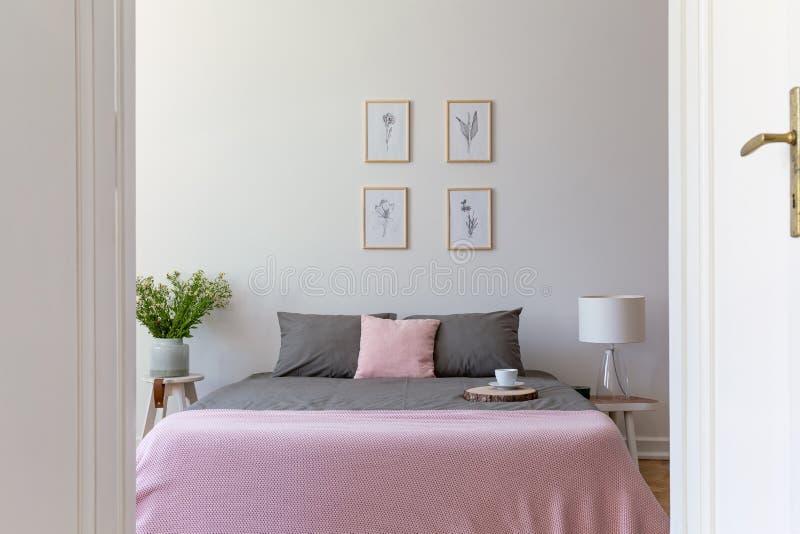 Een mening door een open deur in een binnenland van de pastelkleurslaapkamer met askleurig beddegoed en rooskleurige deken op een stock foto's