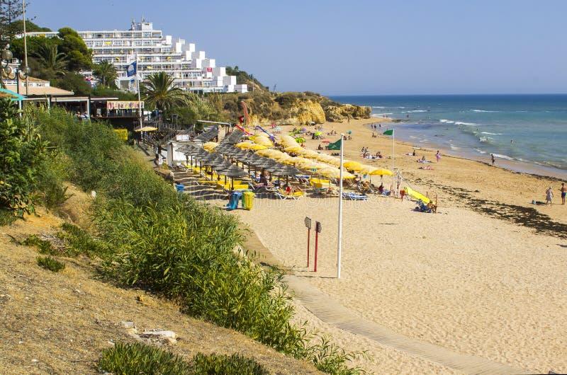 Een mening langs het Strand Albuferia van Oura Praia met zonbedden en zand stock afbeeldingen
