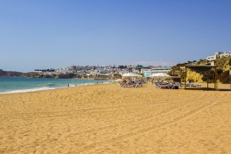 Een mening langs Praia do Inatel beachin Albuferia met zonbedden en zand stock foto