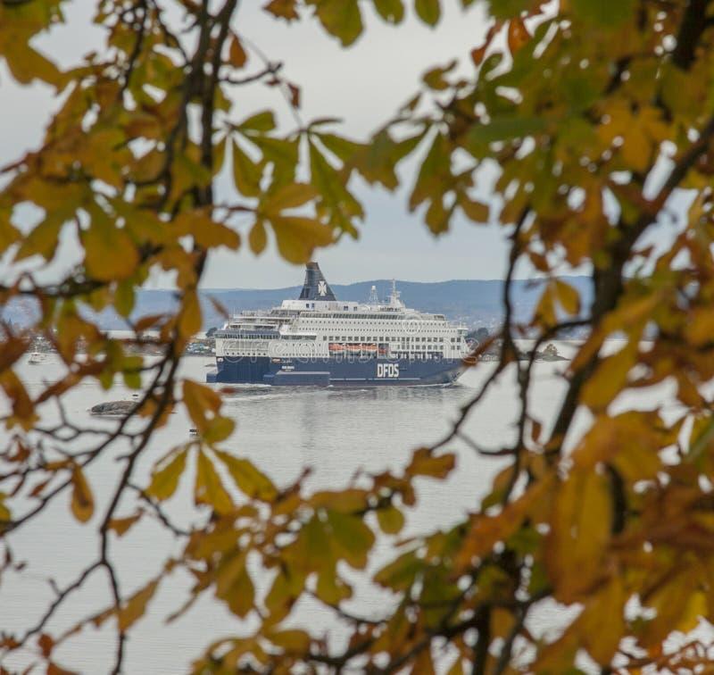 Een mening van de Akershus-Vesting, Oslo, Noorwegen, Europa - fjord en een schip door sommige gele en groene bladeren stock afbeelding