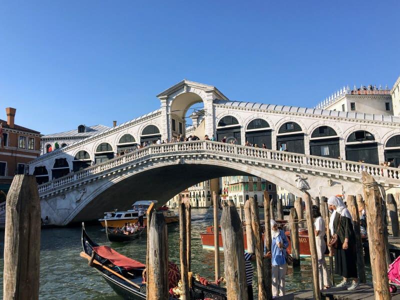 Een mening van de beroemde Rialto-Brug langs Grand Canal in Venetië Italië Toeristen en status op de brug stock foto
