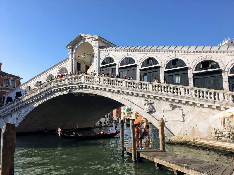 Een mening van de beroemde Rialto-Brug langs Grand Canal in Venetië Italië Toeristen en status op de brug stock fotografie