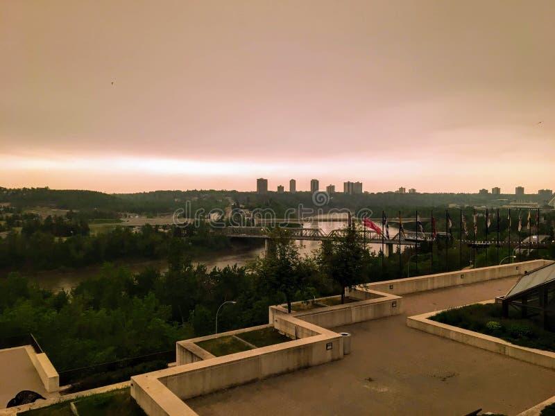 Een mening van van de donkere rokerige wazige oranje en bruine hemel boven de riviervallei binnen in Edmonton van de binnenstad,  royalty-vrije stock afbeeldingen