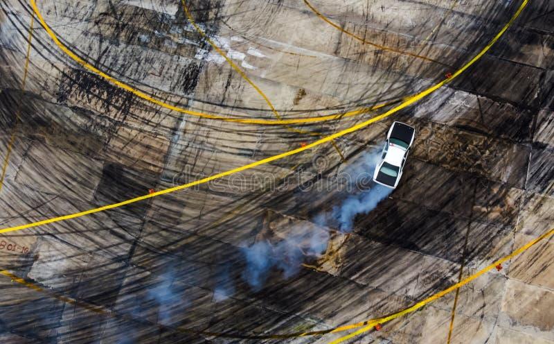 Een mening van de lucht het rennen afwijkingsauto met heel wat rook op stock fotografie
