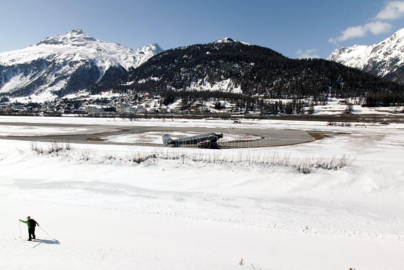 Een mening van een dorp in St Moritz, sneeuw behandelde landschap en berg, een vliegtuig, een mens die in de alpen Zwitserland sk stock afbeelding