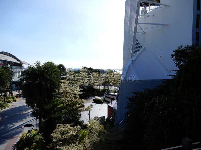 Een mening van een gebouw, groene bomen, een heldere hemel en sommige schepen, Sentosa, Singapore royalty-vrije stock afbeeldingen