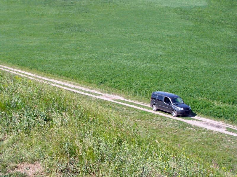 Een mening van hierboven van een auto die langs een landweg in het midden van groene weiden op een zonnige dag berijden Recreatie royalty-vrije stock fotografie