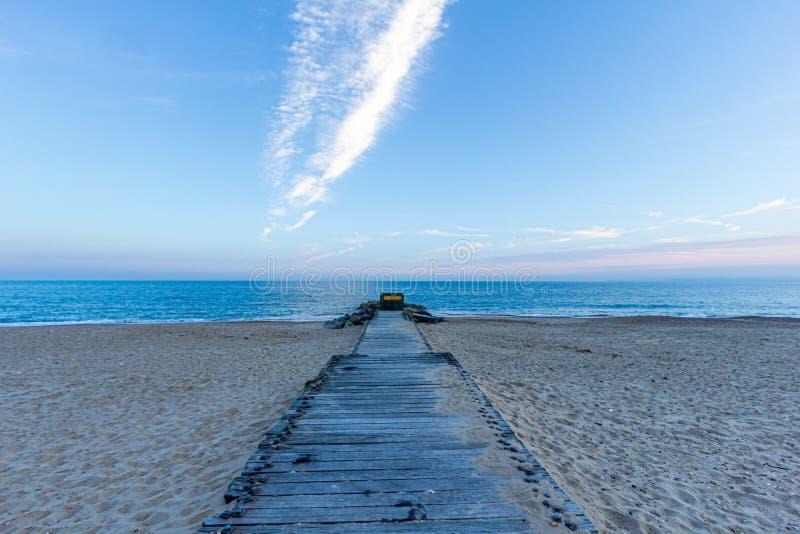 Een mening van een houten ponton op een zandig strand met steenachtige golfbrekergolfbreker en kalme mooie overzees op de achterg royalty-vrije stock fotografie