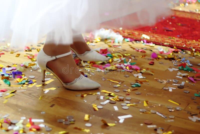Een mening van een houten vloer met een strook van een rood tapijthoogtepunt van muntstukken, confettien en gekleurde documenten  royalty-vrije stock afbeeldingen