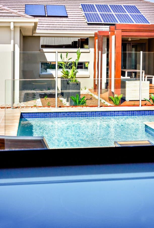 Een mening van een modern zwembad en een huis met zonnepanelen op het dak royalty-vrije stock afbeelding