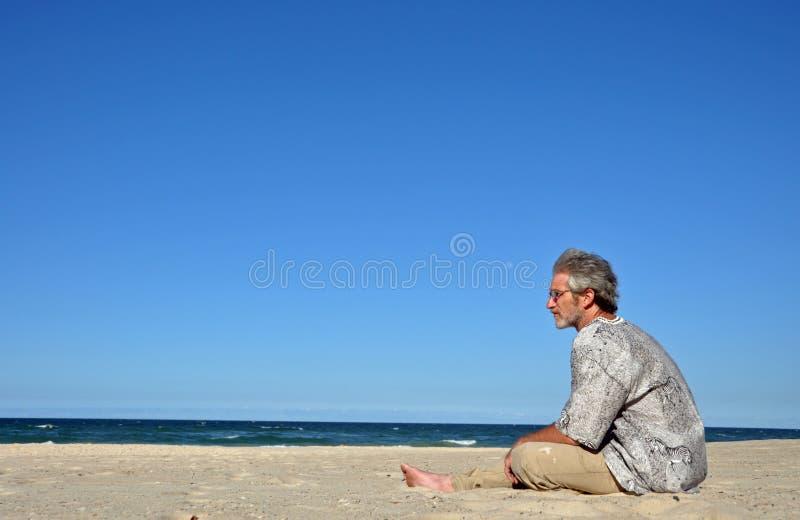Een mens alleen op wit zandig strand stock fotografie